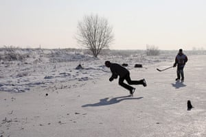 UK weather: A man falls over whilst playing a game of ice hockey on a frozen fen