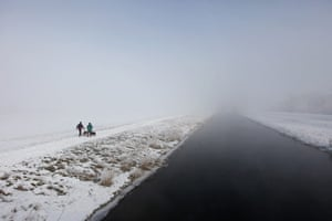 UK weather: A couple walk their dogs in Sutton
