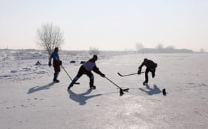 UK weather: A game of ice hockey on a frozen fen in Sutton