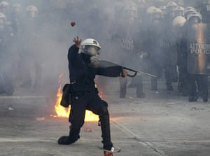 Athens demo: A riot police officer throws a stone at demonstrators