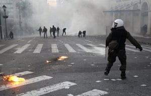 Athens demo: A riot police officer runs past demonstrators