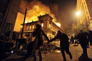 Greece austerity protests: protesters run past a burning building in Athens