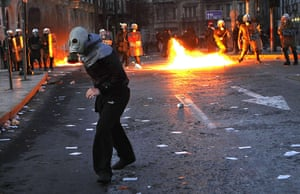 Greece unrest: A protester runs away from police during a violent demo in Athens