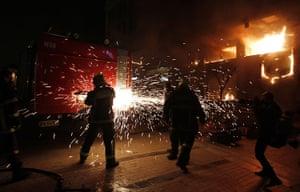 Greece unrest: A Starbucks coffee shop burns, right