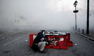 A protester wearing a gas mask shelters himself as he clashes with riot police, Athens