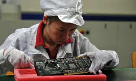 (FILES) A worker inspects motherboards o
