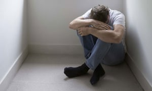 Depressed man with his head on his arms