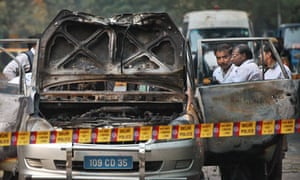Indian police forensic experts investigate the Israeli embassy car hit by a bomb in New Delhi