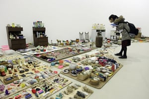 Song Dong installation: A woman examines objects in the installation