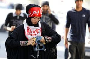Bahrain: An anti-government protester fixes her tear gas mask