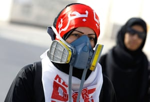 Bahrain: An anti-government protester wearing her gas mask