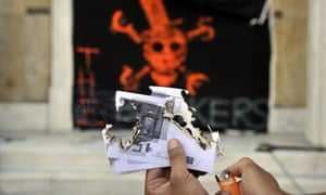 Greek protester setting fire to Euros