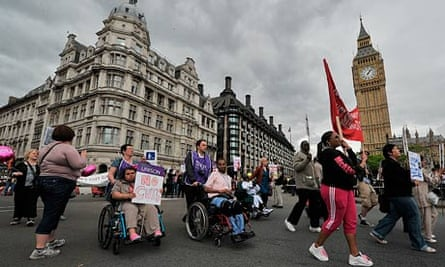 Disabled protestors demonstrate past the