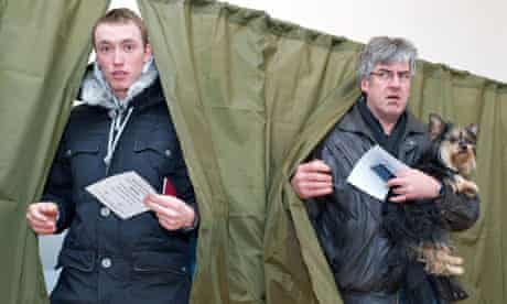 Two men leave polling booths in Latvia