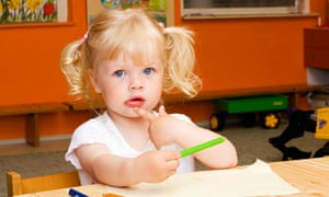 Blond little girl, 2 years, sitting at table with crayons