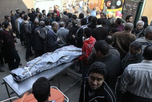 Port Said clashes: Egyptians stand around the body of a victim of football violence, egypt