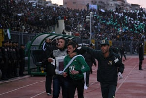 Port Said clashes: A wounded Egyptian fan of Al-Masry is escorted by a medic