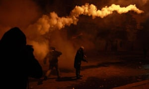 A protester throws a teargas canister back towards police lines in Cairo