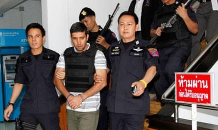 Thai police officers escort Iranian suspect Khazaei at the Metropolitan Police Bureau in Bangkok