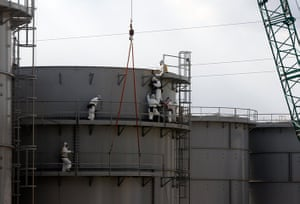 inside Fukushima: workers masks construct water tanks at the powerstation