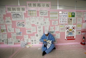 inside Fukushima: a worker in front of an information board
