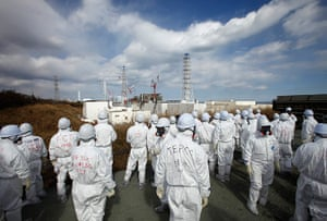 inside Fukushima: members of the media wearing protective suits and masks