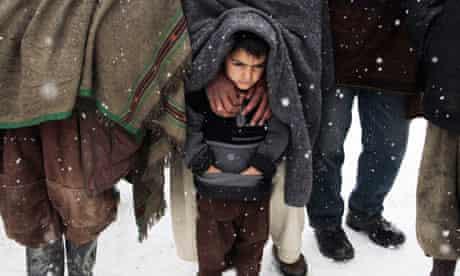 Afghan boy waits for food