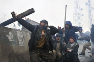Bagram protest: man aims a slingshot