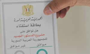 A man displays a ballot card for a draft referendum on the new Syrian constitution