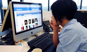 A woman views her profile on Facebook