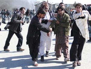 'Qur'an burning' Bagram: Afghans help an injured man