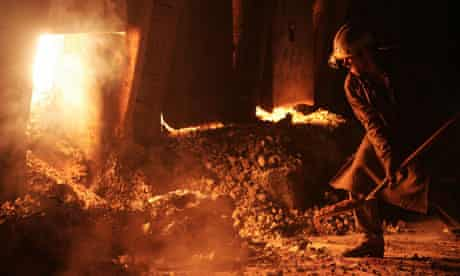 A worker throws coal into a smelting furnace