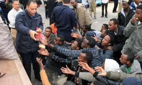A Libyan policeman distributes bread to migrants rescued off boats that sank