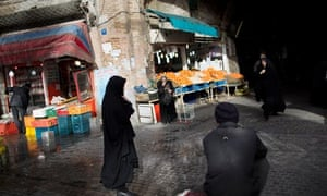 Iranian women walk near a central Tehran bazaar