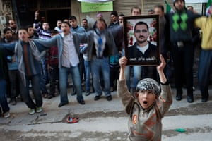 inside northern syria: A boy holds the portrait of a man killed by the Syrian Army