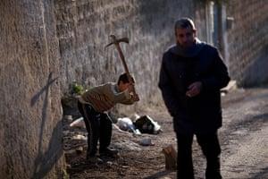 inside northern syria: A boy cuts wood in Kafar Taharim