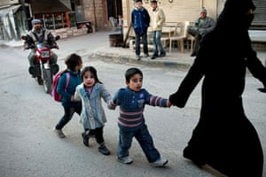 inside northern syria: A woman leads a group of children along street in Kafar Taharim