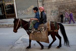 inside northern syria: Children carry firewood on horseback in Kafar Taharim