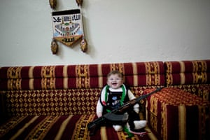 inside northern syria: 6-months old baby, laughs  as it is posed with a machine gun near Idlib