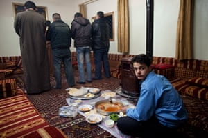 inside northern syria: Mohammed has dinner as supporters of the Free Syrian Army pray near Idlib
