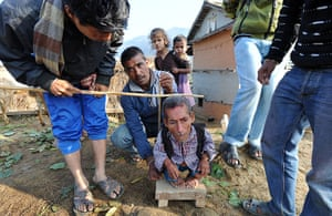 World's shortest man: Dangi, at 56 centimetres in height, stands as villagers measure him