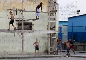 24 hours in pictures: Boys play baseball on a street in Havana