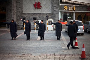 24 hours in pictures: Restaurant security guards practice their guiding gestures, China