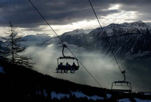 24 hours in pictures: Ski racers sit on the chairlift in the early morning in Crans-Montana