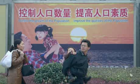 A couple with a small child walk past a propaganda poster promoting the single child policy