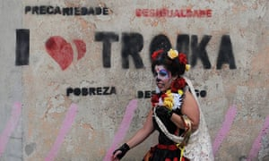 A reveler walks past graffiti about the intervention of the financial troika