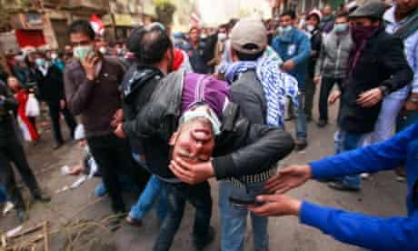 A wounded man is carried away in Cairo during protests after Egypt's football deaths