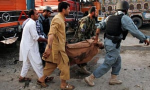 An Afghan civilian is carried away after being killed in a bomb attack in Jalalabad