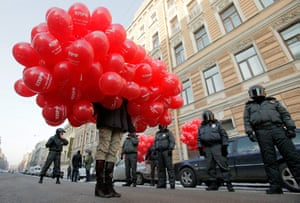 Russia Protest: A protester holding red balloons walks past riot policemen in St Petersburg