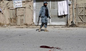 An Afghan policeman patrols the streets of Kandahar after a car bomb blast at the police HQ